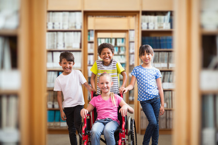 discapacidad: alumno discapacitado lindo que sonríe en la cámara con sus amigos contra la biblioteca Foto de archivo
