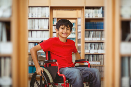 ni�o discapacitado: Retrato de ni�o sentado en la silla de ruedas frente a la biblioteca