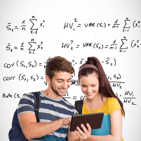 equations: Happy students using tablet pc against maths equations Stock Photo