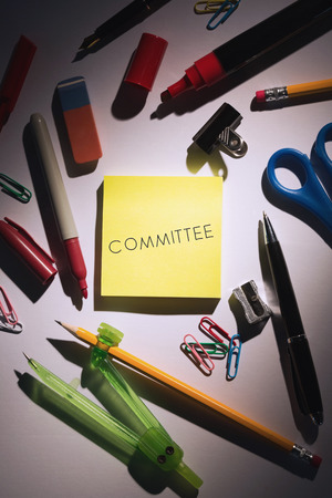 committee: The word committee against students table with school supplies Stock Photo
