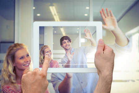 envisioning: Hand holding tablet pc against colleagues envisioning an idea together