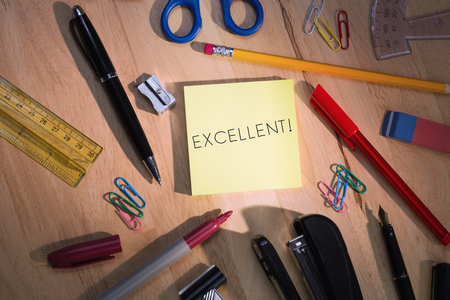 supplies: The word excellent! against students table with school supplies Stock Photo