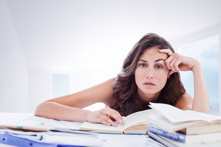 bored student: Bored student doing her homework against bright white hall with columns Stock Photo