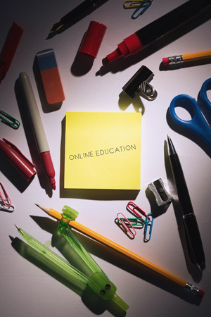 online education: The word online education against students table with school supplies Stock Photo