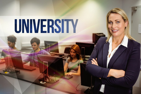 university education: The word university against computer teacher smiling at camera with arms crossed Stock Photo