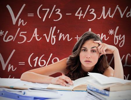 bored student: Bored student doing her homework against desk Stock Photo