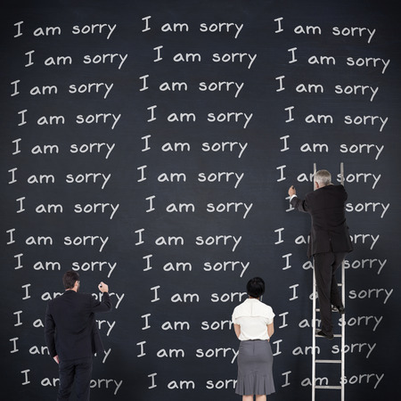 i am sorry: Business team writing against black background