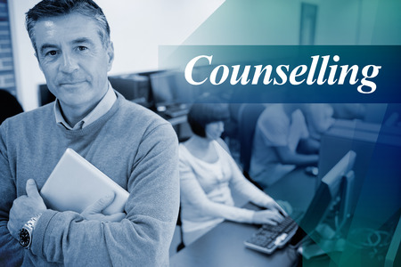 counselling: The word counselling against teacher standing while holding a tablet pc