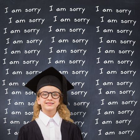 i am sorry: Cute pupil in graduation robe   against black background