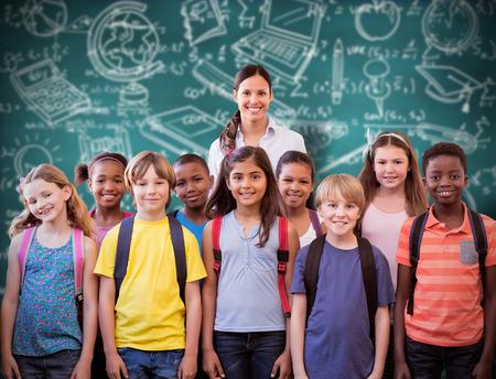 maestra preescolar: alumnos lindos sonriendo a la cámara en el pasillo frente a la pizarra verde