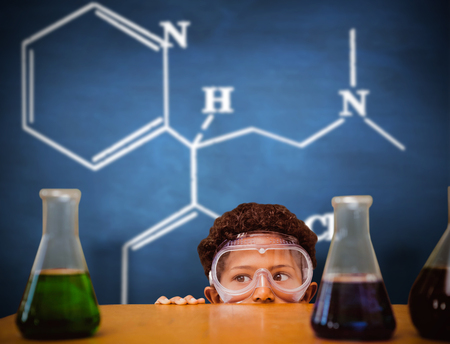 make believe: Cute pupil dressed up as scientist against blue chalkboard Stock Photo