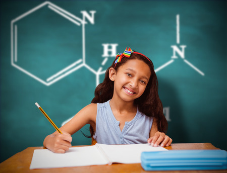 the pupil: Pupil at her desk against green chalkboard Stock Photo
