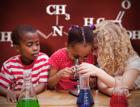children at school: Cute pupil looking through microscope against desk