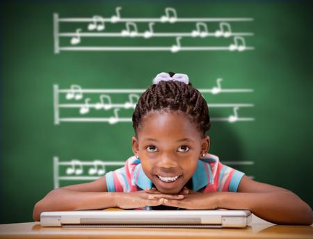 niños en la escuela: Sonriendo alumna sentada en su escritorio contra la pizarra verde