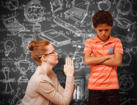 Teacher begging boy against black background Stock Photo