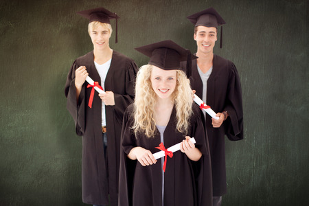 adolescents: Group of adolescents celebrating after Graduation against green chalkboard Stock Photo