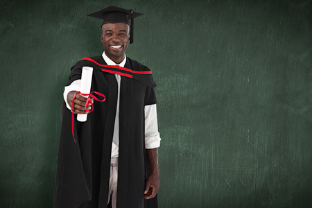 smilling: Man smilling at graduation against green chalkboard