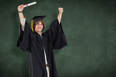 academic robe: Male student in graduate robe raising his arms against green chalkboard Stock Photo