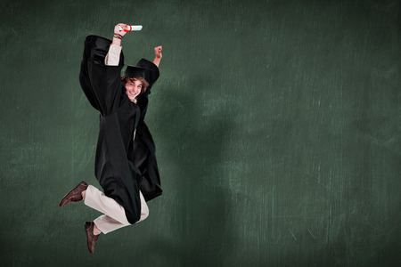 Robe: Happy male student in graduate robe jumping against green chalkboard Stock Photo