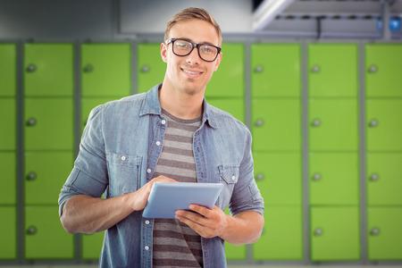 locker room: Student using tablet against locker room Stock Photo