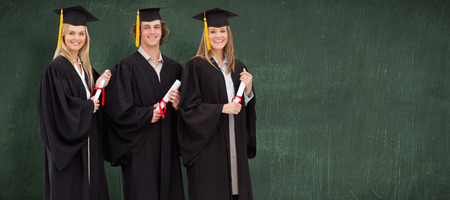 academic robe: Three smiling students in graduate robe holding a diploma against green chalkboard