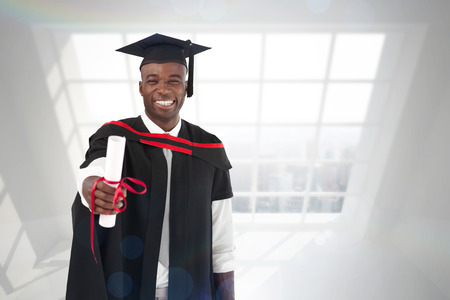 cap and gown: Man smilling at graduation against room with large window showing city Stock Photo
