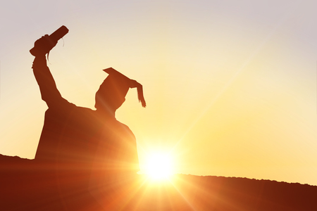 college education: Silhouette of graduate against sun shining Stock Photo