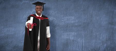 smilling: Man smilling at graduation against blue chalkboard Stock Photo