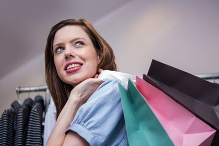 over the shoulder: Woman holding shopping bags over shoulder in fashion boutique