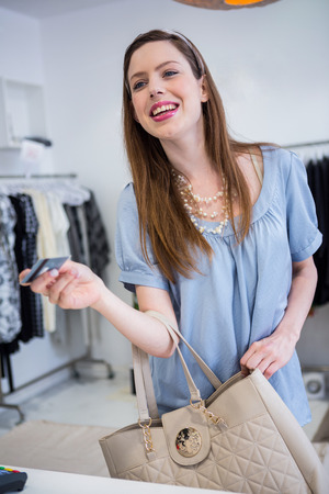 to till: Brunette paying at till with credit card in fashion boutique