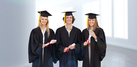 Robe: Three students in graduate robe holding a diploma against modern hallway Stock Photo