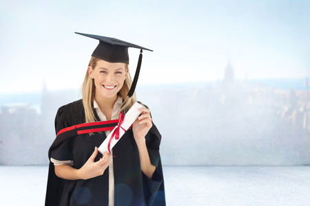 Woman smiling at her graduation  against city scene in a room