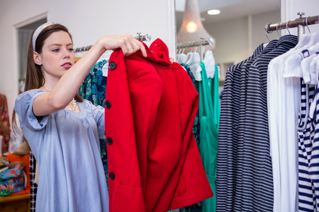 trying: Brunette trying on a red coat in fashion boutique Stock Photo