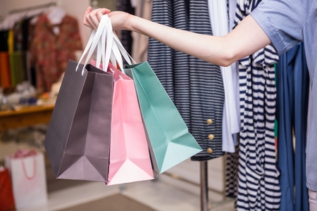 lady shopping: Woman holding shopping bags out in fashion boutique