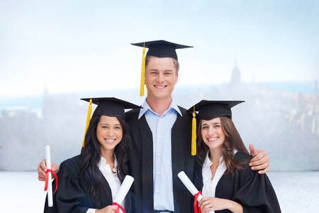 Three friends graduate from college together against city scene in a room Stock Photo