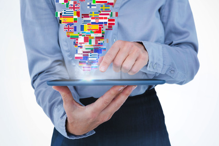 international flags: Businesswoman using her tablet against international flags Stock Photo