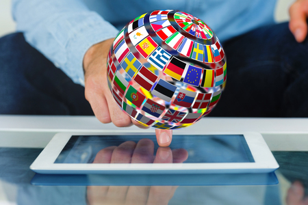 international flags: Close up of finger from man touching tablet against sphere made of flags