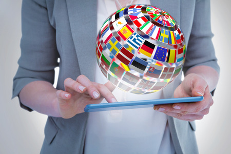 international flags: Close up of woman using tablet against sphere made of flags