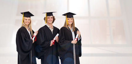 cap and gown: Three smiling students in graduate robe holding a diploma against bright white room with windows Stock Photo
