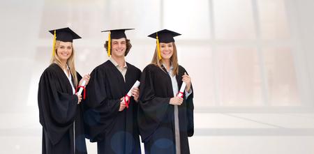toga y birrete: Tres estudiantes sonriente en traje graduado poseedores de un t�tulo contra el cuarto blanco brillante con ventanas