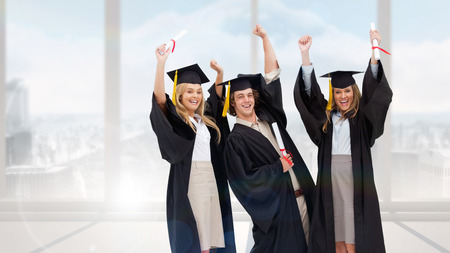 academic robe: Three students in graduate robe raising their arms against bright white room with windows