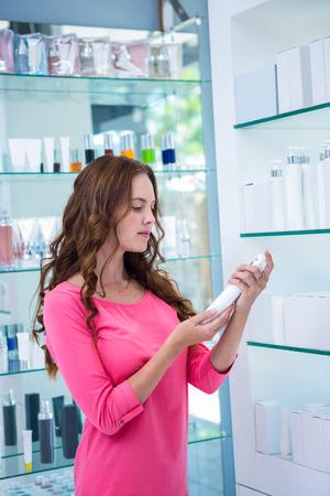 cosmeticos: Mujer bonita de compras para los cosméticos en la farmacia