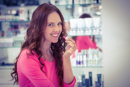 lapiz labial: Mujer bonita que intenta una barra de labios en la farmacia