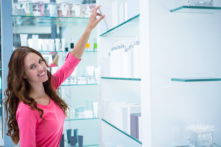 reach customers: Pretty woman shopping for cosmetics at the pharmacy Stock Photo