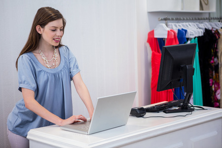 till: Shop worker using laptop by the till in fashion boutique