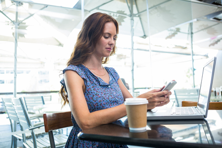 coffee house: Pretty brunette using her laptop in a coffee shop Stock Photo