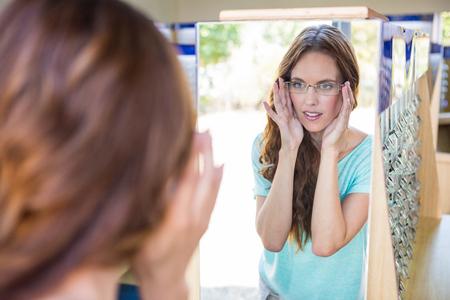 gafas: Mujer bonita de compras para los nuevos vasos en la tienda de optometr�a