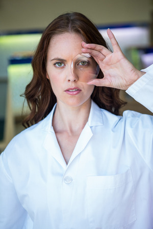 eye service: Serious optician holding up lens at the optometry store Stock Photo