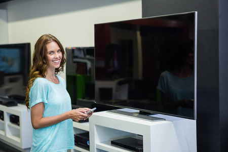 electronics store: Pretty woman shopping for new television at the electronics store