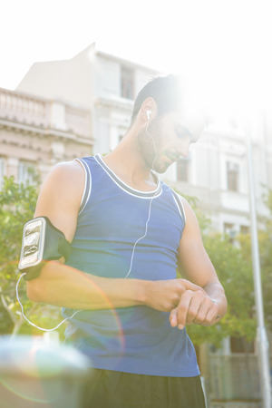 watch city: Handsome athlete checking heart rate watch in the city